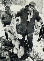 25 Miles by snowmobile from Rupert House, Quebec, brought Angus Whiskeychan, holding a lynx, to the trapper's camp fo Harry Jolly and his family. The camp overlooks the Broadback River that flows through land that will lose its game when the James Bay project is completed.<br /> <br /> 1974<br /> <br /> PHOTO :  Bob Olsen - Toronto Star Archives - AQP