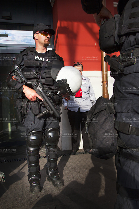 Switzerland. Canton Ticino. Lugano. Railway station. Two police officers from TPO (Transport Police). Both policemen wear the special riot police black uniforms and helmets. One officer holds in his hand a grenade launcher (40 mm BT08).TPO (Transport Police) is the Swiss Federal Railways Police. Swiss Federal Railways (German: Schweizerische Bundesbahnen (SBB), French: Chemins de fer fédéraux suisses (CFF), Italian: Ferrovie federali svizzere (FFS)) is the national railway company of Switzerland. It is usually referred to by the initials of its German, French and Italian names, as SBB CFF FFS. 2.06.2017 © 2017 Didier Ruef