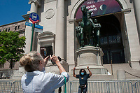 """NEW YORK CITY, NY - JUNE 22 : Rose Browne (right) gesture in triumph for a photograph in front of controversial statue of Theodore Roosevelt in front of the American Museum of Natural History on June 22, 2020 in New York City. In the context of widespread protests against racism sparked by the killing of African-American George Floyd by police, the American Museum of Natural History announced it would remove a bronze equestrian statue of Theodore Roosevelt flanked by an African and Native American man depicted in a subservient position. Ms. Browne stated,  """"I am happy the statue will come down. You know, for people like me to see this past commemorated is offensive."""" This statue has long been criticized and protested by anti-racism activists for its white supremacist iconography (Photo by Stephen FerryVIEWpress)"""