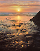 Fall Creek flowing into the Pacific Ocean at sunset at Hug Paoint State Park Oregon