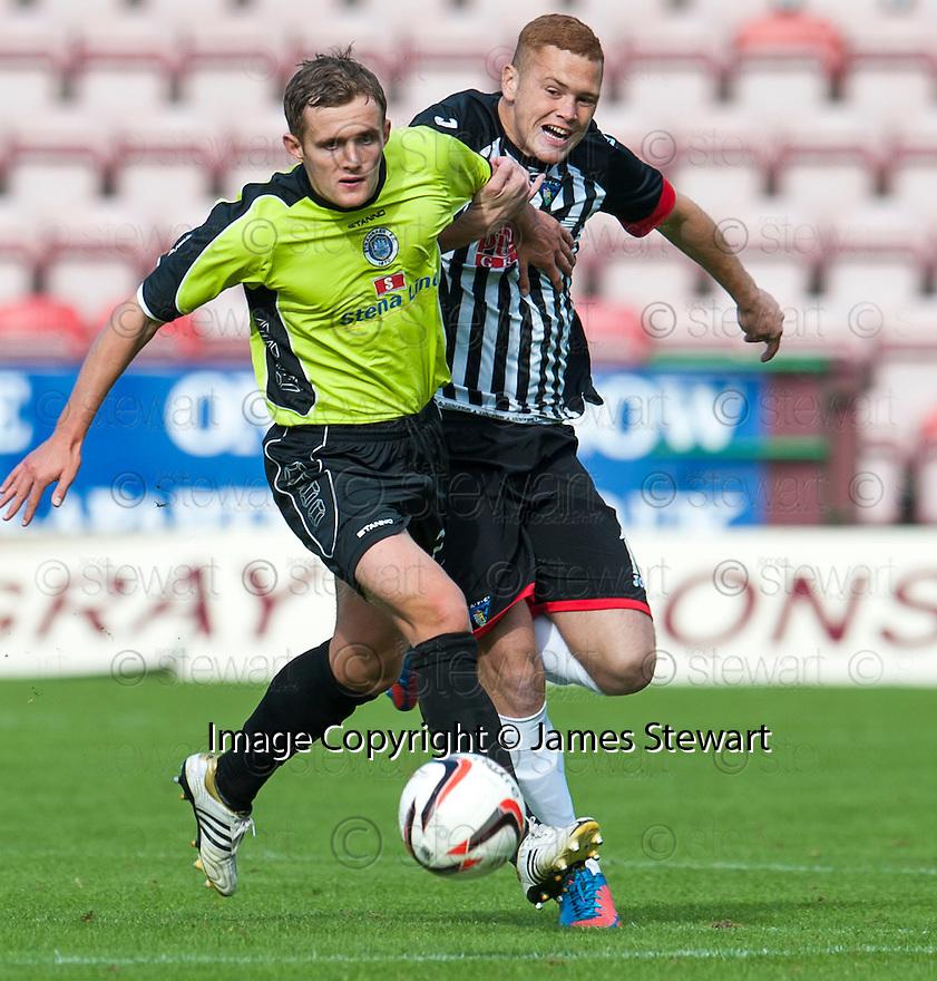 Stranraer's Scott Rumsby holds back Pars' Ryan Thomson.