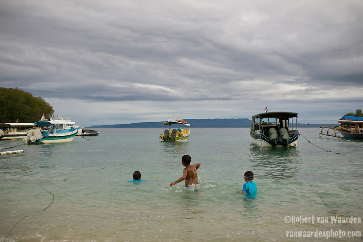 Three kids enjoy swimming in the warm waters of Padangbai in Bali, Indonesia. A grey sky and fishing boats fill the background.