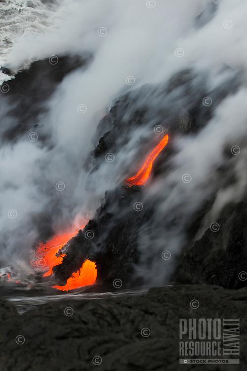 Silky lava flow enters the ocean from a cliff near Hawai'i Volcanoes National Park and the Kalapana border, Big Island.