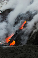 Silky lava flow enters the ocean from a cliff near Hawai'i Volcanoes National Park and the Kalapana border, Big Island.