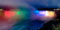 Amazing Niagara Falls horseshoe panorama, at twilight, with mist and water colored with rainbow lights, in Canada
