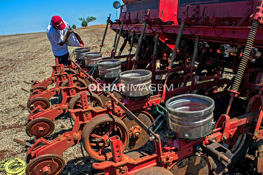 Trabalhador carrega sementes de milho uma máquina agricola em plantio direto, em fazenda de Bela Vista do Paraiso. Parana. 2013. Foto de Alf Ribeiro.
