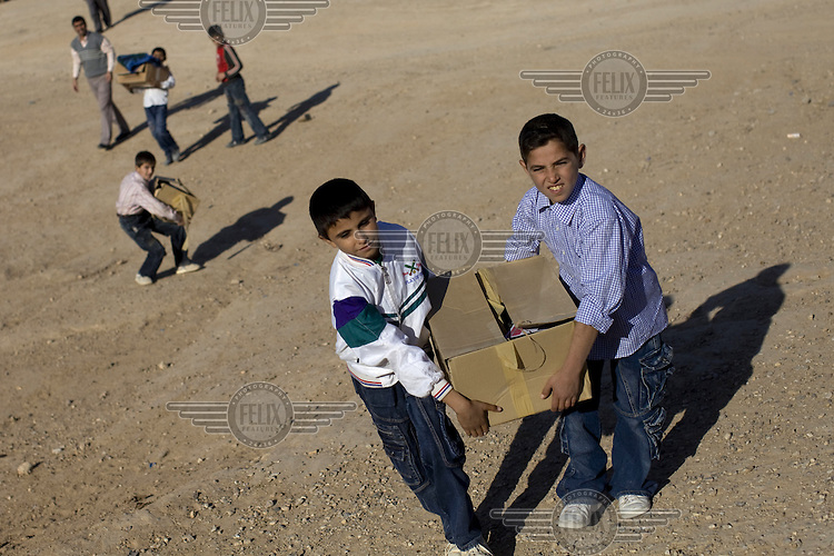 Children carrying boxes of humanitarian aid received from the US Army in Said Bashier.