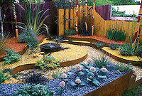 Dry Gardening with an Australian theme: Landscaping xeriscaping raised beds in copper, succulents australian style dry drought garden, raised beds, curving edges, totem pole ornaments, allium ornamental onions, exotic, mixed hardscaping mulch materials, mulching styles, stones, pebbles, wood, drought tolerant perennials, shrubs, trees, flowers