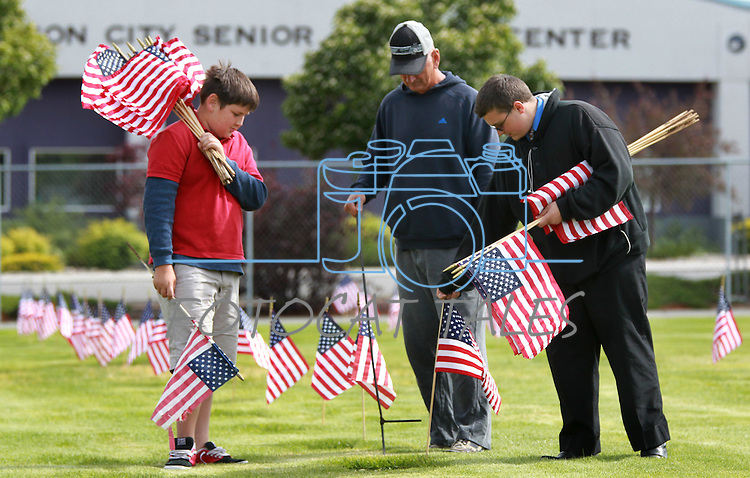 Volunteers, from left, Tyler Baker, 9, Wayne Baker and Casey Ussery, 16, place flags on the graves of veterans at the Lone Mountain Cemetery in Carson City, Nev., on Friday, May 25, 2012. Volunteers from the D.A.V., American Legion, Carson High School ROTC and Boy Scout Troop 145 placed more than 1,400 flags on the graves of veterans in honor of Memorial Day..Photo by Cathleen Allison