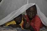 Two children peek out from under a Permanet long lasting insecticide treated mosquito net in the Garki area of Abuja. Sleeping under a mosquito net every night prevents malaria, which is transmitted through the bite of an infected mosquito.  Globally, malaria kills 1,000,000 people every year, most of them pregnant women and children under five.