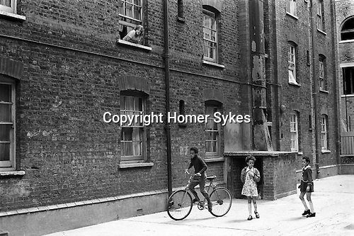 Great Eastern Buildings.  Peabody Housing Estate. Tower Hamlets Whitechapel east London UK 1970s. Multiracial Britain, immigrant children playing in the communal area of the block of flats. 1975  <br /> <br /> Jacqueline (Jackie) Harris. Looking out of the window, Jackie was 13 or 14 at the time.