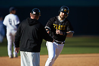West Virginia State Yellow Jackets assistant coach Greg Keaton shakes hands with Matt Harrison (32) as he rounds third base during the game against the Catawba Indians at Newman Park on February 9, 2020 in Salisbury, North Carolina. The Indians defeated the Yellow Jackets 15-9 in game one of a doubleheader.  (Brian Westerholt/Four Seam Images)