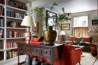 The living room is furnished with a pair of opposing sofas and a free-standing console table, while one wall is lined with bookshelves