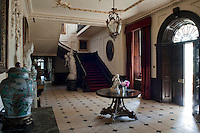 The entrance hall is furnished with a pair of marble-topped giltwood console tables displaying a collection of Chinese urns and sculpture