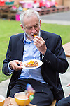 © Joel Goodman - 07973 332324 . 24/09/2016 . Liverpool , UK . JEREMY CORBYN eats pizza breads he made during a visit to Beaconsfield Community House in Birkenhead , following his victory declaration . The centre provides clothes and food that would otherwise be destined for waste from supermarkets , to local residents in need . Photo credit : Joel Goodman