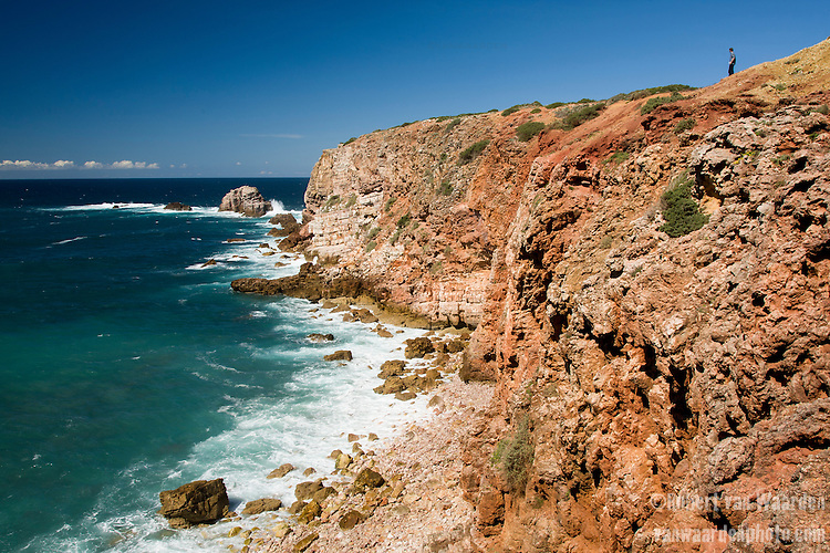 A man stands on the red and orange Bordeira headland in the South West of Portugal.