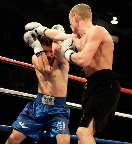 GLASGOW, SCOTLAND - MARCH 10: Damon Jones (black shorts) lands a punch on Liam Griffiths (blue shorts) during a Middleweight contest on the Ricky Burns undercard at the Braehead Arena on March 10, 2012 in Glasgow, Scotland. (Photo by Rob Casey/Getty Images)