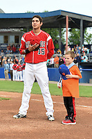 Batavia Muckdogs shortstop Hiram Martinez (15) stands with a young fan during the national anthem before a game against the Mahoning Valley Scrappers on June 20, 2014 at Dwyer Stadium in Batavia, New York.  Batavia defeated Mahoning Valley 7-4.  (Mike Janes/Four Seam Images)