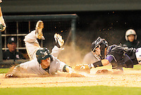 Catcher Zach Greenwell (4) of the Furman Paladins applies the tag late on Jordan Keur (6) of the Michigan State Spartans in a game on February 25, 2012, at Fluor Field in Greenville, South Carolina. (Tom Priddy/Four Seam Images)