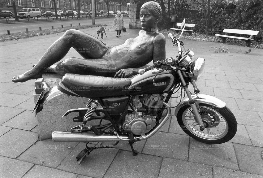 Germany. Hamburg. Street life. A bronze sculpture of a naked woman and a 500 Yamaha motorcycle. The motorbike parked on the sidewalk is missing the back wheel. An elderly woman walks with her dog on a leash. Hamburg, officially the Free and Hanseatic City of Hamburg, is the second-largest city in Germany. © 1988 Didier Ruef