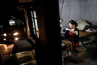A 50 year old rural migrant works in a garment sweatshop on the outskirts of the southwestern Chinese megapolis of Chongqing. They often work through the nights, earning 1,000 - 6,000 yuan per month depending on work load, a decent income compared with subsistence farming. For many, this is a long and arduous step in the transition from farming to urban living. China is hoping by relocating farmers into cities they would start to buy food, making a break from the cycle of farmers consuming only what they produce. The Chinese government plans to move 250 million rural residents into urban areas over the coming dozen years though it is unclear whether people want to move and where the money for this project will come from. Further urbanisation is meant to drive up consumption to counterbalance an export orientated economy and end subsistence farming but the drive to get people off the land is causing tens of thousands of protests each year. /Felix Features