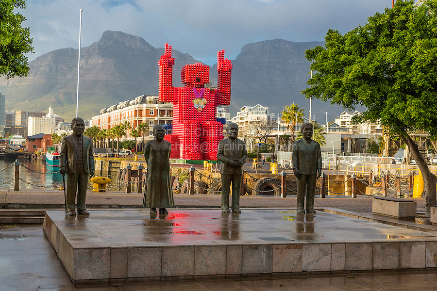 """South Africa, Cape Town.  Nobel Square Statues of Albert Luthuli, Desmond Tutu, FW de Klerk, and Nelson Mandela.  Sculptor Claudette Schreuders.  In background is the """"Lego Man"""" sculpture made of 4200 plastic  Coca Cola crates.  Designed by Porky Hefer."""