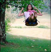 Young woman swinging on tree swing.