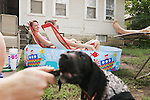 """CHAD PILSTER •Hays Daily News<br /> <br /> (left to right) Fort Hays State University students Dakota Thomas, from Garden City, plays with his dog Ranger, a 10 week labrador and pointer, while Ashley Bowles and her sister Lacey Bowles, from Lindsborg, lounge in the pool as A.J. Brown, from Topeka, reads a book on  Monday, June 17, 2013, along West 6th St. in Hays, Kansas. Brown, said a friend and himself bought the pool on a whim one day when they were in WalMart and thought """"We need a pool."""""""