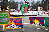 """Switzerland. Basel. Oustide the St. Jakobshalle. A group of Doegyal / Shugden followers are protesting against the existence of His Holiness the Dalai Lama and write on a banner to stop lying. The pro Dalai Lama followers show tibetan flags and a poster with the words """" We stand with His Holiness the Dalai Lama. The 14th and current Dalai Lama is Tenzin Gyatso, recognized since 1950. He is the current Dalai Lama, as well as the longest-lived incumbent, well known for his lifelong advocacy for Tibetans inside and outside Tibet. Dalai Lamas are amongst the head monks of the Gelug school, the newest of the schools of Tibetan Buddhism. The Dalai Lama, also called """" Ocean of Wisdom"""" is considered as the incarnation of Chenresi, the Bodhisattva of compassion who is also the protective deity of Tibet. The Tibetan flag, also known as the """"snow lion flag"""" and the 'Free Tibet flag', was a flag of the military of Tibet, introduced by the 13th Dalai Lama in 1912 and used for the same capacity until 1959. Designed with the help of a Japanese priest, it reflects the design motif of the Japanese military's Rising Sun Flag. Since the 1960s, it is used a symbol of the Tibetan independence movement. 8.02.2015 © 2015 Didier Ruef"""