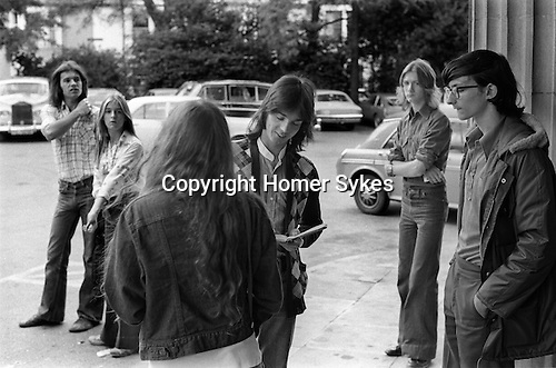 """Jimmy signing autographs outside Southampton Hotel 1975 Wings Tour UK. Linda daughter and tutor behind left. McCartney two Rolls Royce parked in hotel car park. The photographs from this set were taken in 1975. I was on tour with them for a children's """"Fact Book"""". This book was called, The Facts about a Pop Group Featuring Wings. Introduced by Paul McCartney, published by G.Whizzard. They had recently recorded albums, Wildlife, Red Rose Speedway, Band on the Run and Venus and Mars. I believe it was the English leg of Wings Over the World tour. But as I recall they were promoting,  Band on the Run and Venus and Mars in particular."""