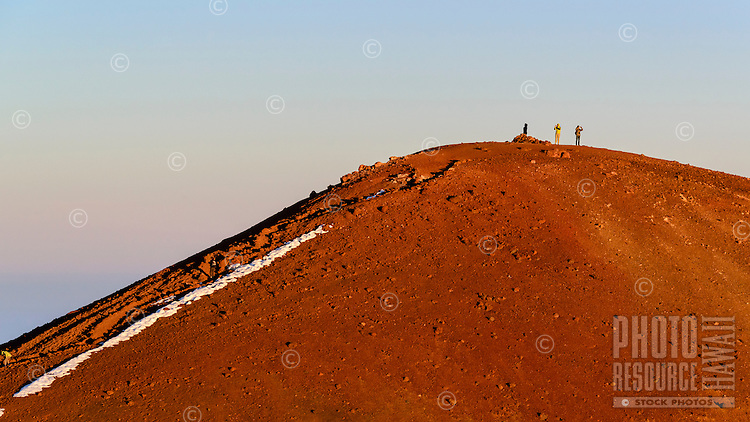 Three hikers lit by the setting sun, Mauna Kea, Island of Hawai'i.