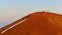 Three hikers lit by the setting sun, Mauna Kea, Island of Hawai'i.