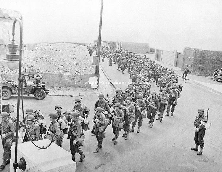 America soldiers, equipped with full pack and extra allotments of ammunition, march down an English street to their invasion craft for embarkation, on June 6, 1944 for their historic second front assault on the french coast. (AP Photo)