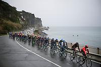 peloton racing along the Mediterranean on a rainy day<br /> <br /> 106th Milano - San Remo 2015