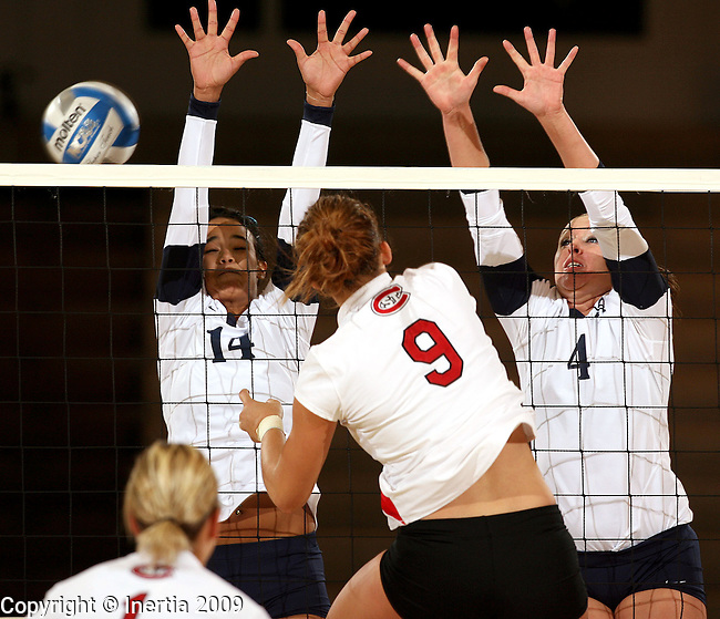 SIOUX FALLS, SD - SEPTEMBER 29:  Blythe Johnson #14 and Megan Bezdicek #4 of Augustana double team for a block of Kayla Tschida #9 from St. Cloud State University in the third game of their match Tuesday night at the Elmen Center. (Photo by Dave Eggen/Inertia).