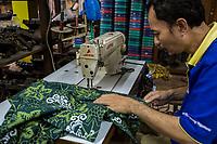 Yogyakarta, Java, Indonesia.  Batik Workshop.  Man Sewing Batik Fabric.