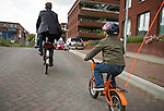 Albert van der Hem, owner and founder of Blix Consulting rides with his son through the streets of Utrecht. Albert has been involved with the sustainable energy industry and in particular wind energy for over 10 years.