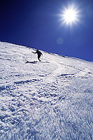 A skier glides down the slope of Mauna Kea on the Big Island of Hawaii with a blazing white sun and blue sky in the background.