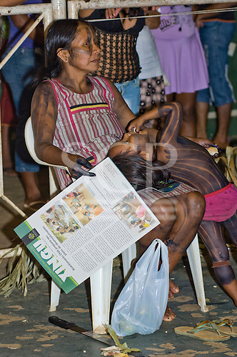 """Altamira, Brazil. """"Xingu Vivo Para Sempre"""" protest meeting about the proposed Belo Monte hydroeletric dam and other dams on the Xingu river and its tributaries. Kayapo woman with her daughter holding a printed report from Y Ikatu Xingu."""