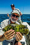 Hal Yeager shows off a neon green tripletail fish with Justin Wallheiser as the boat captain at Shell Point.