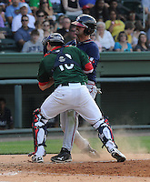 Catcher Blake Swihart (10) of the Greenville Drive is knocked off his feet at home plate but stays upright to make the tag for an out on Jakob Dalfonso (9) of the Rome Braves on May 6, 2012, at Fluor Field at the West End in Greenville, South Carolina. Swihart was a first-round pick (26th overall) by the Boston Red Sox in the 2011 First-Year Player Draft. Greenville won, 11-3. (Tom Priddy/Four Seam Images)