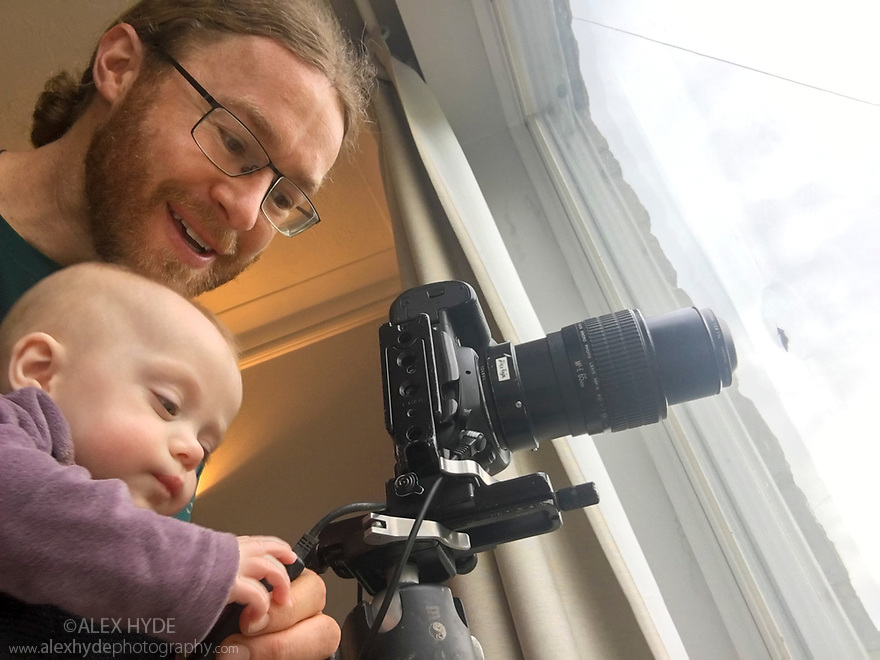 Photographer Alex Hyde working from home whilst carrying baby daughter during the Covid-19 Pandemic, April 2020.