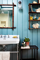The tongue and groove cladding that lines the walls of the bathroom has been painted a duck egg blue