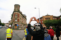 Pictured: A group of levitators walk the High Street towards the Palace Theatre in Swansea. Sunday 16 July 2017<br /> Re: A team of highly trained Levitators harness their psychic forces to raise The Palace Theatre on the High Street in Swansea, south Wales, as part of the Troublemakers Festival.<br /> The theatre was built in 1888 as a traditional music hall, named originally the 'Pavilion'. During its lifetime, the building has been used as a bingo hall as well as a gay nightclub.<br /> The Grade II Listed building is one of just two purpose-built music halls left standing in the whole of the UK.<br /> In the early years of the 20th century stars like Charlie Chaplin, Lilly Langtry, Marie Lloyd and Dan Leno filled the venue.<br /> Sir Anthony Hopkins made his first professional stage appearance there in 1960 with Swansea Little Theatre's production of 'Have A Cigarette'.<br /> Also in the early 1960s, Morecambe and Wise were booked. Ken Dodd was the last stand-up comedian to appear there before it became nightclub in the 1970s.<br /> It was also the first place in Wales to show a silent picture and remained undamaged by the blitz that destroyed much of Swansea city centre during the Second World War.<br /> Eventually the theatre was sold for £300,000 to a property company, but in 2010 it was still derelict and actor Edward Fox joined a campaign to have it restored.