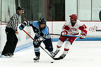 BOSTON, MA - JANUARY 04: Ida Kuoppala #26 of University of Maine brings the puck forward as Jesse Compher #7 of Boston University closes during a game between University of Maine and Boston University at Walter Brown Arena on January 04, 2020 in Boston, Massachusetts.