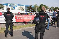 """Nach den pogromartigen Ausschreitungen gegen eine Fluechtlinsunterkunft im saechschen Heidenau am Freitag den 21. August 2015 durch Anwohnerinnen der Ortschaft, kamen am Samstag de 22. August 2015 ca. 250 Menschen in die Ortschaft um ihre Solidaritaet mit den Gefluechteten zu zeigen.<br /> Am Vorabend hatten Rassisten, Nazis und Hooligans sich zum Teil Strassenschlachten mit der Polizei geliefert um zu verhindern, dass Fluechtlinge in einen umgebauten Baumarkt einziehen. Ueber 30 Polizisten wurden dabei verletzt.<br /> Bis in die Abendstunden des 22. August blieb es trotz spuerbarer Anspannung um die Unterkunft ruhig. Im Laufe des Tages wurden immer wieder Gefluechtete mit Reisebussen gebracht was von den wartenenden Heidenauern mit Buh-Rufen begleitet wurde. Vereinzelt wurde auch """"Sieg Heil"""" gerufen, was die Polizei jedoch nicht verfolgte.<br /> Kurz vor 23 Uhr griffen Nazis und Hooligans dann wie am Vorabend die Polizei mit Steinen, Flaschen, Feuerwerkskoerpern und Baustellenmaterial an. Die Polizei mussten mehrfach den Rueckzug antreten, scheuchte den Mob dann von der Fluechtlingsunterkunft weg. Dabei wurden auch wieder Traenengasgranaten verschossen. Mindestens ein Nazi wurde festgenommen.<br /> Im Bild: Die Polizei hat die antirassistische Kundgebung umstellt.  Im Hintergrund der zur Erstaufnahme umgebaute Baumarkt.<br /> 22.8.2015, Heidenau<br /> Copyright: Christian-Ditsch.de<br /> [Inhaltsveraendernde Manipulation des Fotos nur nach ausdruecklicher Genehmigung des Fotografen. Vereinbarungen ueber Abtretung von Persoenlichkeitsrechten/Model Release der abgebildeten Person/Personen liegen nicht vor. NO MODEL RELEASE! Nur fuer Redaktionelle Zwecke. Don't publish without copyright Christian-Ditsch.de, Veroeffentlichung nur mit Fotografennennung, sowie gegen Honorar, MwSt. und Beleg. Konto: I N G - D i B a, IBAN DE58500105175400192269, BIC INGDDEFFXXX, Kontakt: post@christian-ditsch.de<br /> Bei der Bearbeitung der Dateiinformationen darf die Urheberkennzeichnung"""