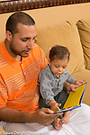 16 year old toddler boy sitting on couch with father looking at book together, pointing at illustration in book