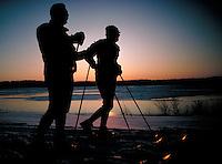 Young adult male and female pause to converse while cross country skiing along the Susquehanna River at sunset. Couples. Harrisburg Pennsylvania United States Riverfront Park.