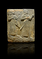 Hittite relief sculpted orthostat stone panel of Royal Buttress. Basalt, Karkamıs, (Kargamıs), Carchemish (Karkemish), 900-700 B C. Warriors. Anatolian Civilisations Museum, Ankara, Turkey.<br /> <br /> Two figures are seen, each with a long dress, a thick belt and curled hair. The figure in front carries a spear in his left hand and a long sword at his waist, and the figure behind carries an axe in his left hand and a quiver on his back.   <br /> <br /> Against a black background.