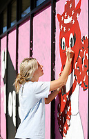 Artist Brogan Stafford paints a University of Arkansas Razorback themed window display Monday, October 12, 2020, for Fringe Clothing at The Academy at Frisco in Fayetteville. The window display coincides with the University of Arkansas Homecoming Celebration that will include a Homecoming football game October 17 between the Razorbacks and the University of Mississippi at Donald W. Reynolds Razorback Stadium. Check out nwaonline.com/201013Daily/ and nwadg.com/photos for a photo gallery.(NWA Democrat-Gazette/David Gottschalk)